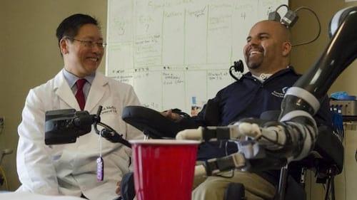 Tetraplégico levanta um copo com braço mecânico controlado por implante