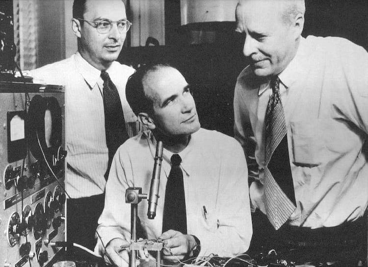 Uma das fotos da ocasião do Nobel na qualShockley adonou-se de um microscópio alheio no momento exato para que parecesse o mais importante do trio. à sua esquerda John Bardeen e à direita Walter Brattain