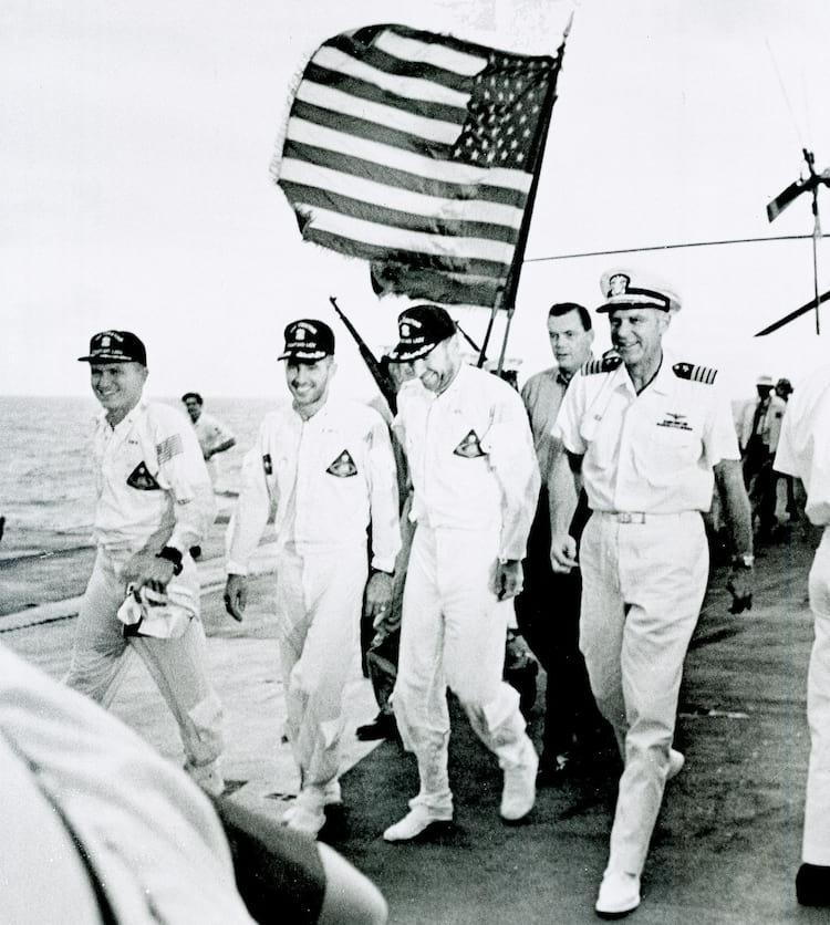 Os astronautas da Apollo 8 e o oficial comandante do navio de recuperação USS Yorktown caminham pelo tapete vermelho da plataforma de vôo após a recuperação do splashdown no Oceano Pacífico