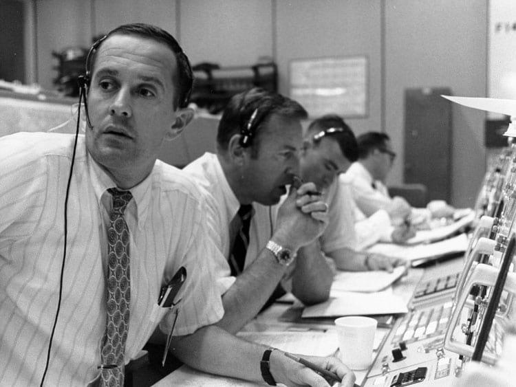 CAPCOM Charlie Duke (em primeiro plano) com o comandante reserva Jim Lovell (ao centro) durante o pouso tenso do Apollo 11