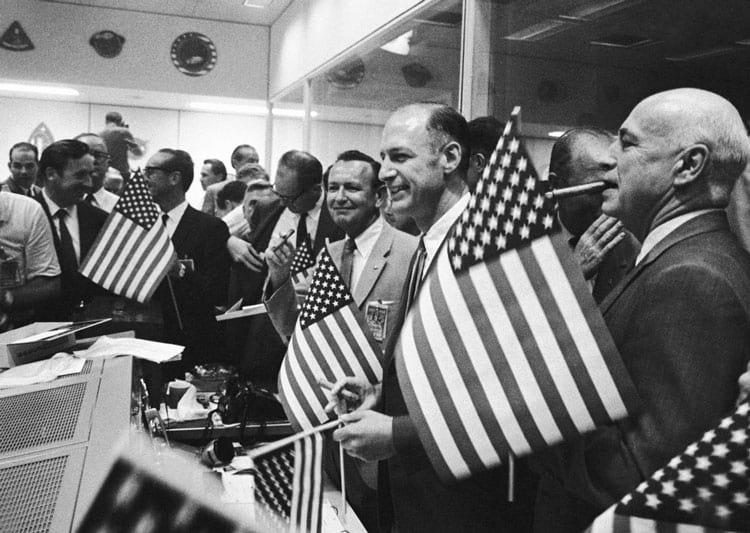Chris Kraft, no centro, segurando um charuto no alto, comemora o retorno da tripulação da Apollo 11 à Terra em 24 de julho de 1969. À sua direita estão George Low e Robert Gilruth