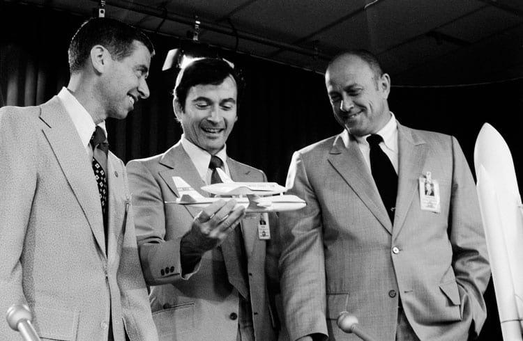O gerente do programa Space Shuttle Bob Thompson, à direita, é mostrado em 1974 com Aaron Cohen e o astronauta John Young. Young está segurando um modelo do ônibus em sua aeronave