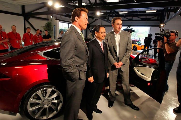 O então governador da Califórnia, Arnold Schwarzenegger, o CEO da Toyota, Akio Toyoda, e Elon Musk, posam na frente de um Tesla Model S na inauguração da nova fábrica da Tesla