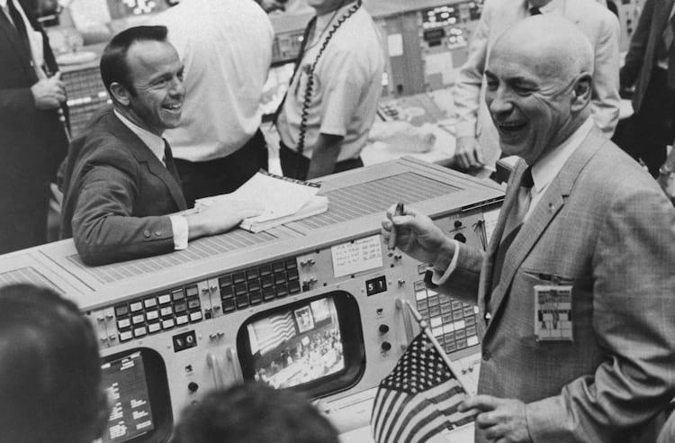 Charutos e bandeiras dos EUA decoram o Centro de Controle da Missão em Houston em 26 de maio, após a conclusão bem-sucedida da missão Apollo 10. Entre os celebrantes estão Alan Shepard (à esquerda), que foi o primeiro homem americano no espaço, e Robert Gilruth (à direita), diretor do Centro Espacial