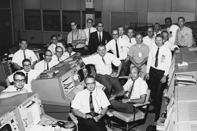Um grupo de gênios de óculos, gravatas e com seus bolsos de camisa bem protegidos, debruçados sobre consoles retro-futuristas deslumbrantes em um quarto escuro e nebuloso com fumaça de cigarro e tensão. Essas são as pessoas que levaram ohomem à Lua