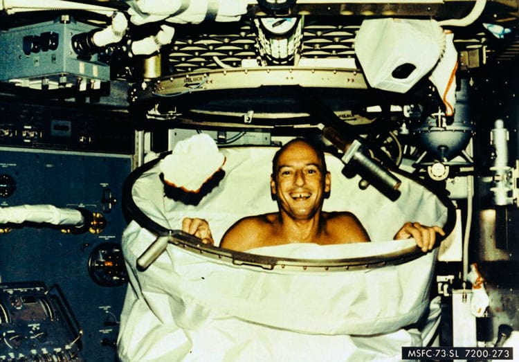 Charles Conrad, Jr., comandante do Skylab-2, sorri depois de um banho quente no chuveiro nos aposentos da tripulação do Orbital Workshop da estação espacial Skylab. Ao implantar o chuveiro, a cortina do chuveiro foi puxada do chão e presa ao teto. A água veio através de um chuveiro com botão de pressão ligado a uma mangueira flexível. A água foi retirada por um sistema de vácuo.