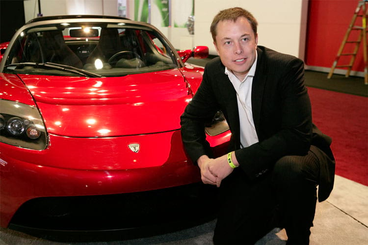 Um jovem Elon Musk posa ao lado de um das primeiras unidades do Tesla Roadster