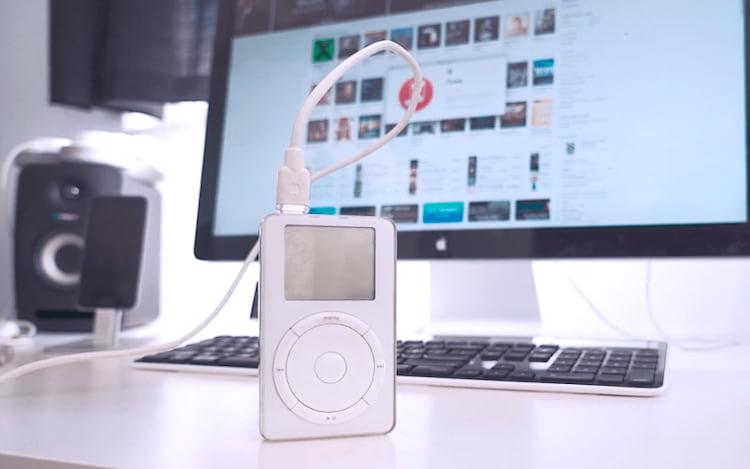 Primeira geração do iPod com iTunes ao fundo